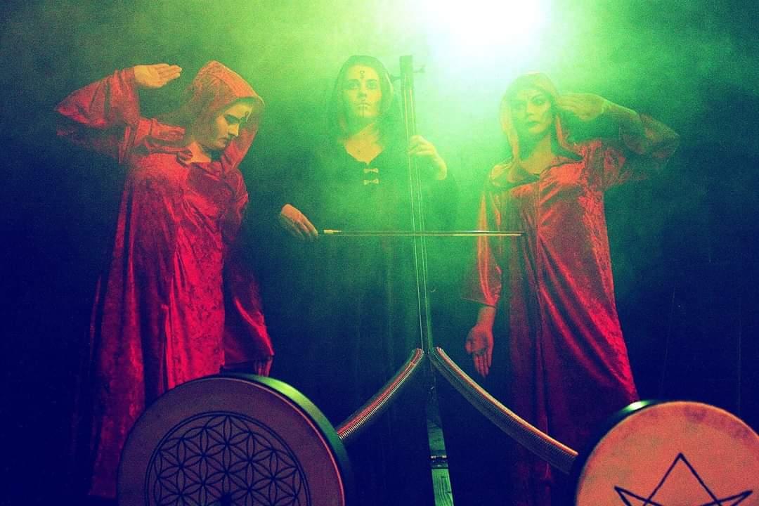 Kaapunaiset Elli Turkka, Mari Melakari ja Anni Majava. Kuvan soitin on Okkultismi-trilogiaa varten tehty Yaybahar.